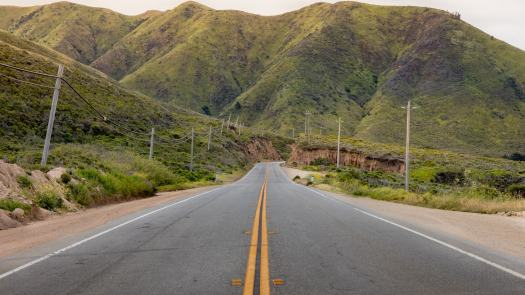 an open road with mountains in the distance