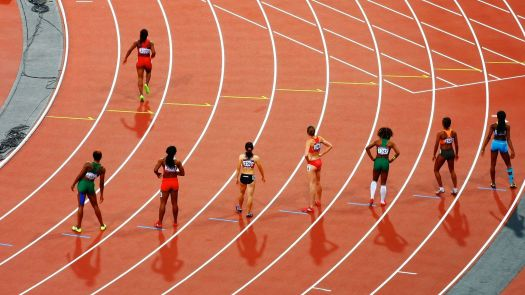 Athletes are seen standing on the start line of a race.