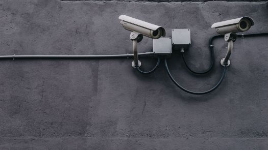 A pair of security cameras are mounted on a wall.