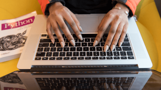 Hands on a keyboard with a Python book