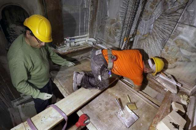 © Provided by AFP Greek preservation experts place back the marble slab stone that covered the Tomb of Jesus, where his body is believed to have been laid, after it was removed for 3 days to allow the team to do restoration works