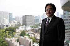 Iwata poses for a photo after an interview in Tokyo