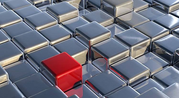 Un cube rouge parmi des cubes métaliques.