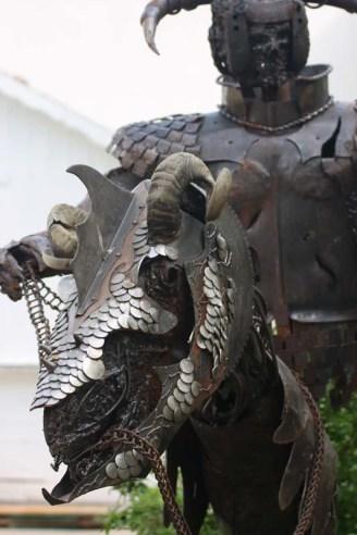 Statue metallique d'un cavalier squelette et de la tête de son dragon.
