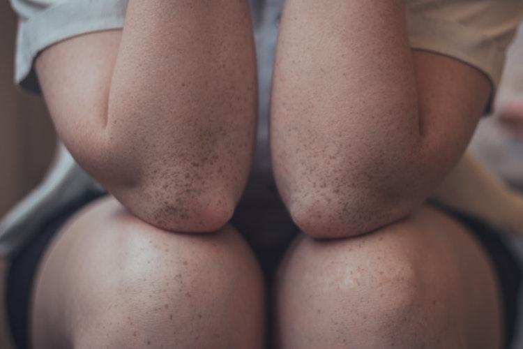 Adolescente assise avec des genoux croisés
