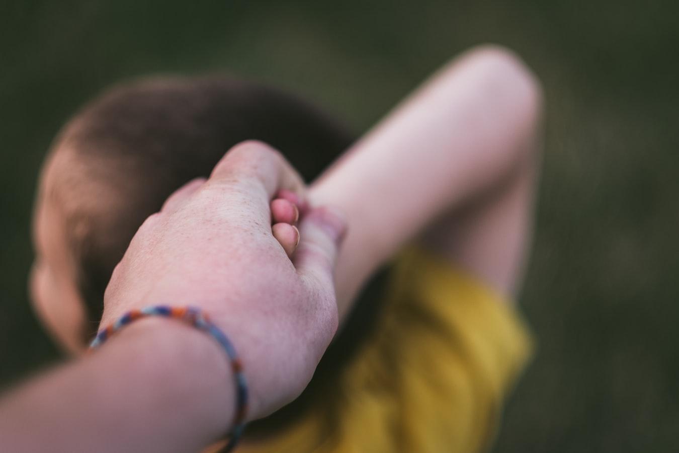 Un enfant retenu par le bras par un adulte