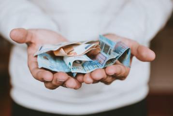 Un homme tenant des billets d'euro.