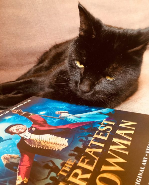 The Greatest Showman book plus Dennis the cat