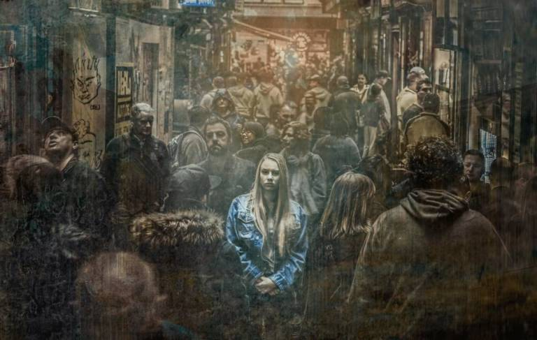 Woman alone in a crowd wondering how to be alone and happy