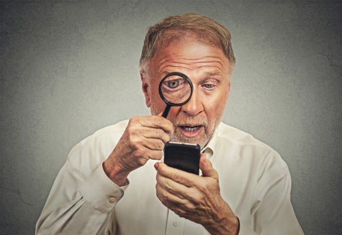 An old man is looking at a website on his phone using a magnifying glass.
