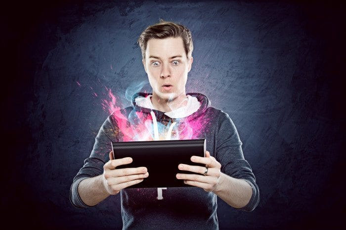 A young man looking astounding by what's going on in his tablet.