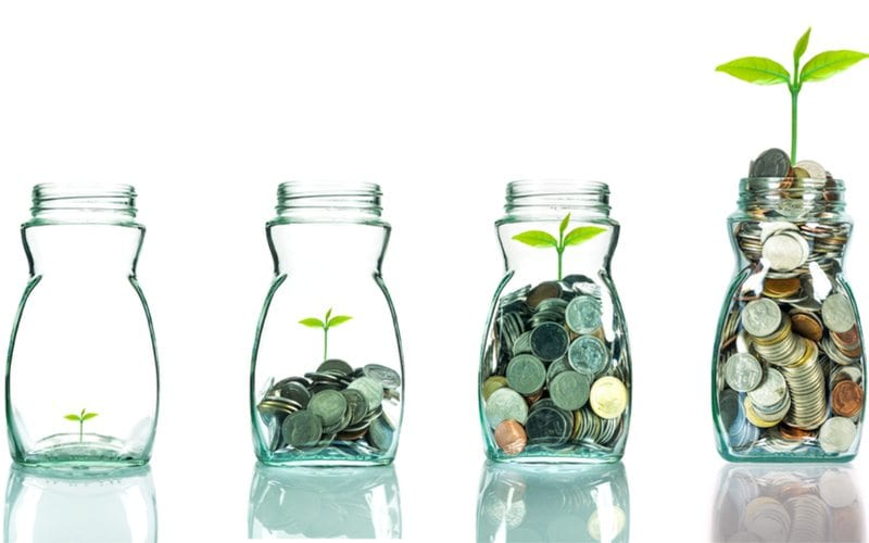 Plant growing from coins in a jar