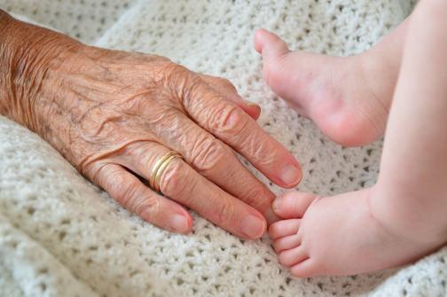 赤ちゃんの足を触ろうとするおばあちゃんの手