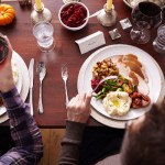overhead-of-two-men-eating-holiday-meal-142589503-59663c633df78c160ee528cf