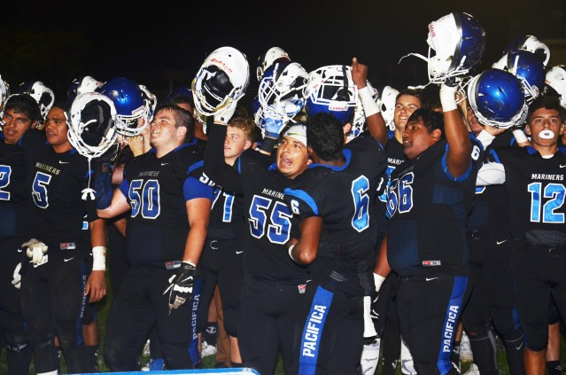 PACIFICA players raise their helmets in triumph after defeating city rival Garden Grove 38-7 Friday night (OC Tribune photo).