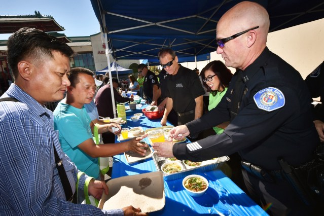 GARDEN GROVE PD Capt. Travis Whitman helps serve free meals that includes a drink and Pho (a type of Vietnamese soup) during the Viet-CARE Pho-Covery Celebration at the Asian Garden Mall in Westminster. Photo by Steven Georges/Behind the Badge OC