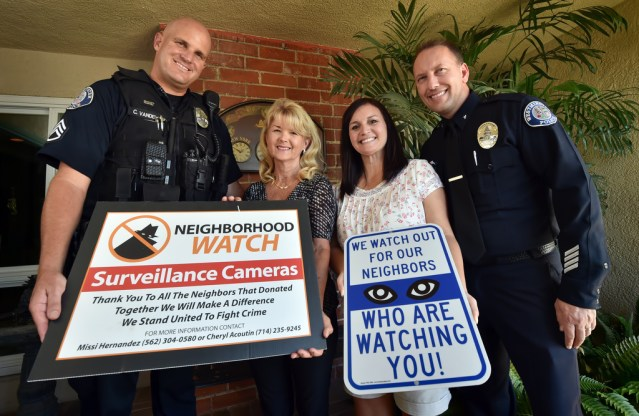 Sgt. Cord Vandergrift, left, and Cmdr. Cameron Knauerhaze of Westminster PD, right, show their support for Cheryl Acoutin and Missi Hernandez of the Sol Vista Neighborhood Watch organization and their ability to raise money and install surveillance cameras that keep an eye on the local streets. (Photo by Steven Georges/Behind the Badge OC).