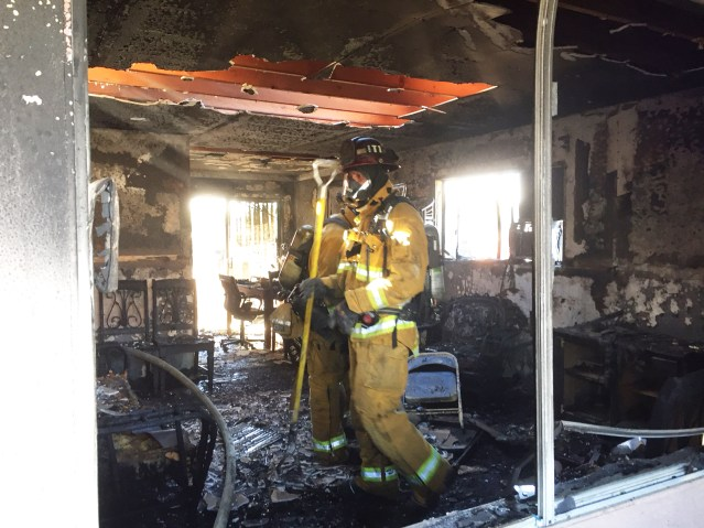 FIREFIGHTERS inside the flame-gutted apartment hit by a blaze Saturday morning in Garden Grove (GGFD photo).