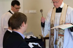 Fr Robinson sprinkles holy water on the vestments
