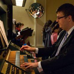 Aaron James accompanies on the organ.