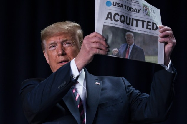 Trump holding a newspaper announcing his acquittal.