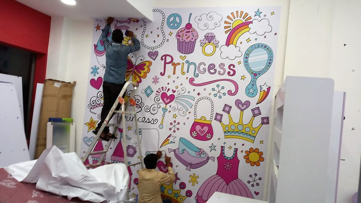 Two men pasting a full-sized wall sticker for children's bedroom