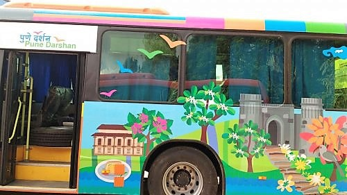 Vehicle prints pasted on the side of a tourist bus showing clip arts of famous monuments in Pune