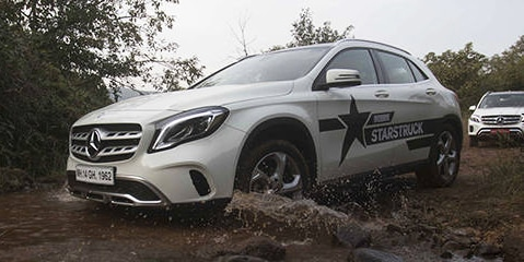 Mercedes company branding and printing on a car racing over a muddy road
