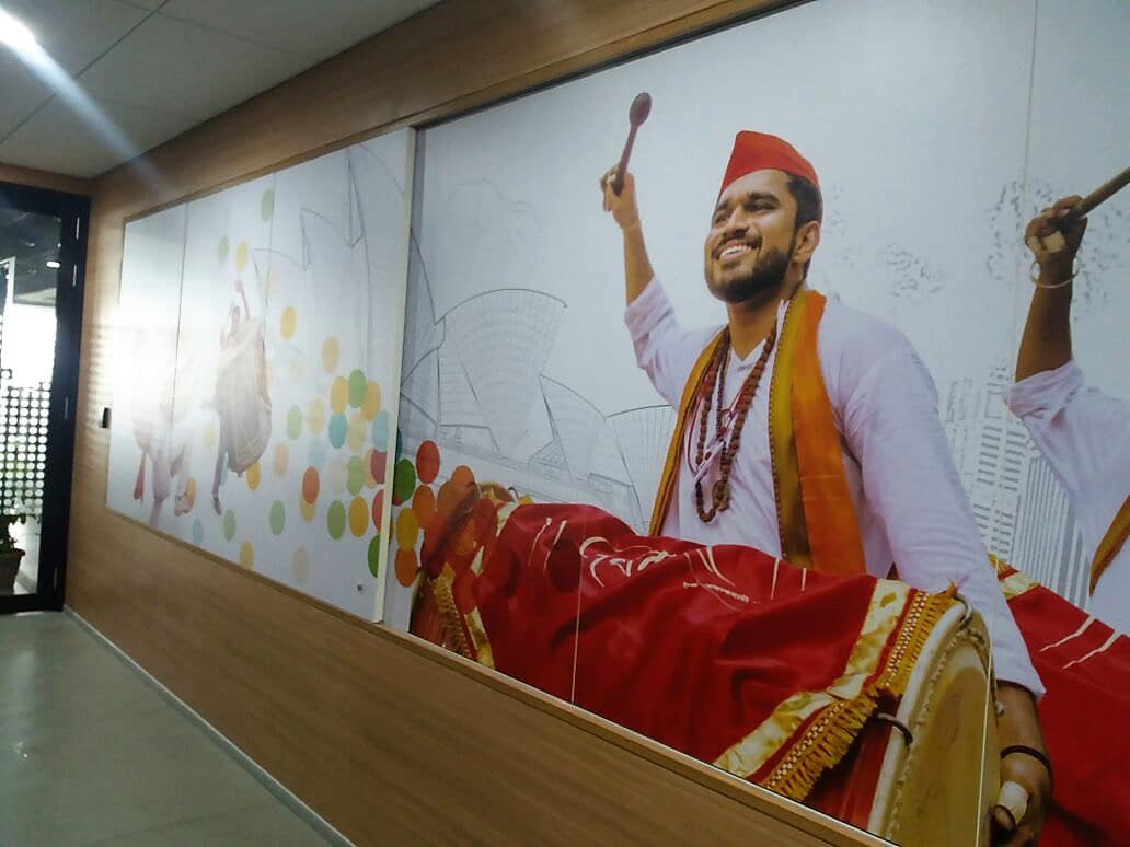 Large-sized custom wallpaper showing a man drumming a dhol. The print is pasted in a corporate office to enhance its interior decor.