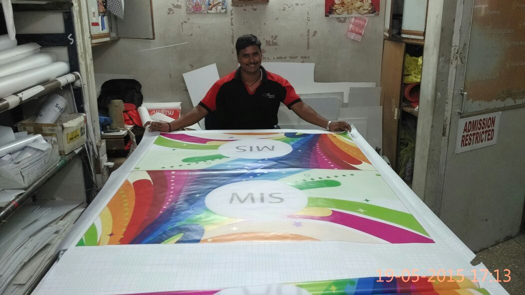 person laying out a large piece of cloth on which the custom design of a company's flag has been printed