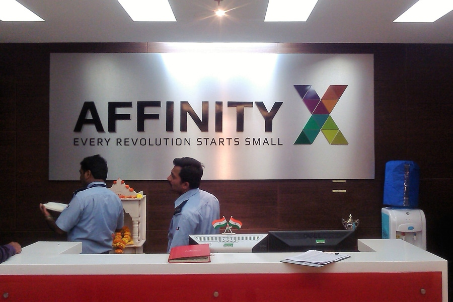 Laser cut acrylic name board displaying the name and logo of the Affinity X company installed on an ACP panel and displayed in the reception area of their office