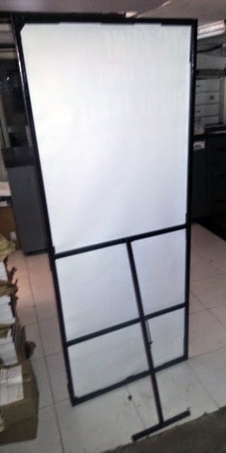 back view of a large life sized sunboard standee supported by a metal frame which can be folded