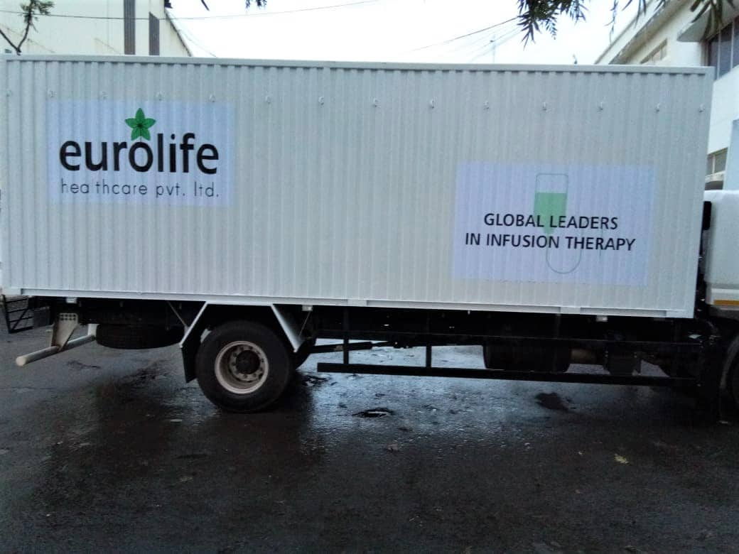 The uneven corrugated side panel of a large container truck is branded using specialised printable vehicle vinyls