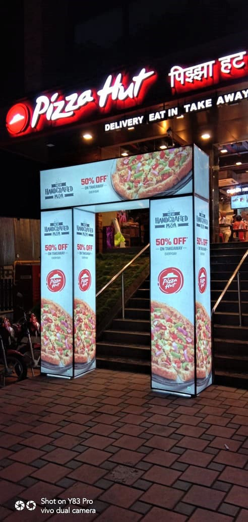 a printed arch gate glowing in the night in front of the Pizza Hut franchisee in a mall