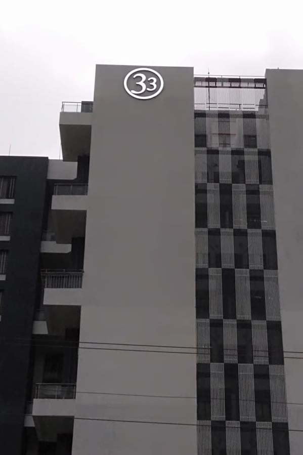 Logo in the shape of the number 33 fabricated from acrylic and metal letters glowing with LEDs and installed as a sky sign on the side of a tall residential building