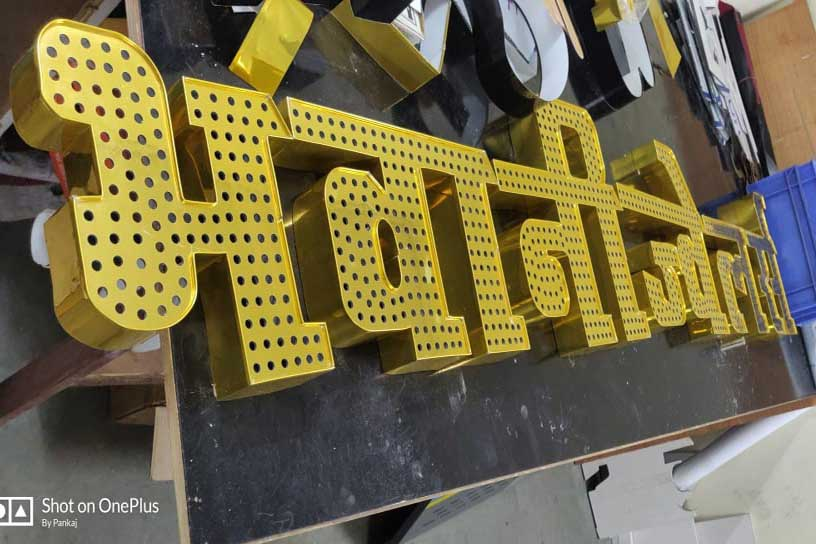Sign letters being fabricated out of gold finish metal with holes drilled on the top surface to insert open dot LEDs