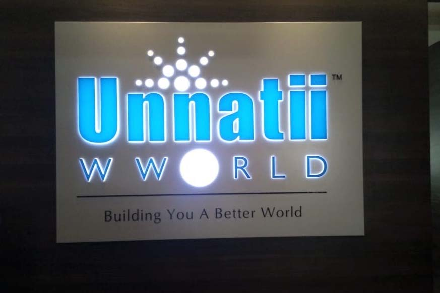 White aluminium composite board with incut acrylic letters for the Unnati world shop sign board. The sign is lit up with blue and white colored LED modules