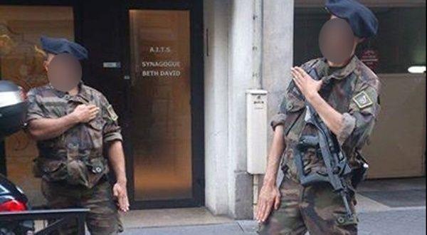 Franska soldater gör quenelle hälsningen framför den synagogan i Paris de är satt att vakta.