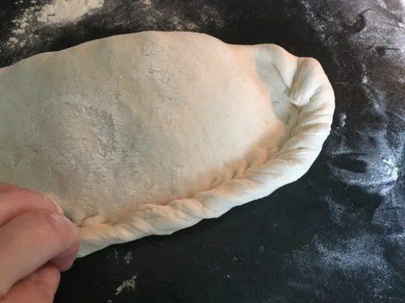 Pinching edges of calzone to seal it