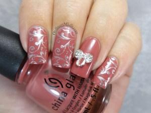 Silver bows and swirls nail art
