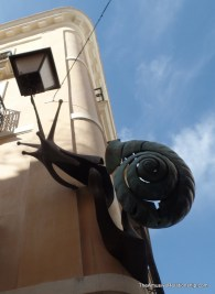 Snail sculpture climbing a building