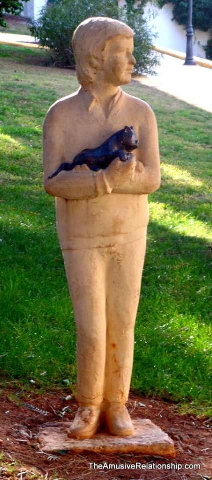 An odd statue of a boy and his cat in the city park