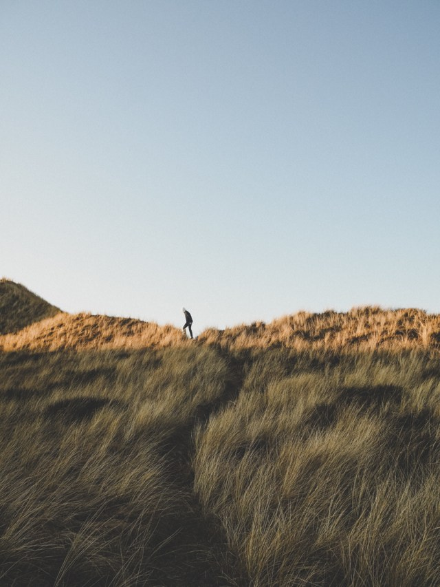 Person walking atop sand dunes to beach