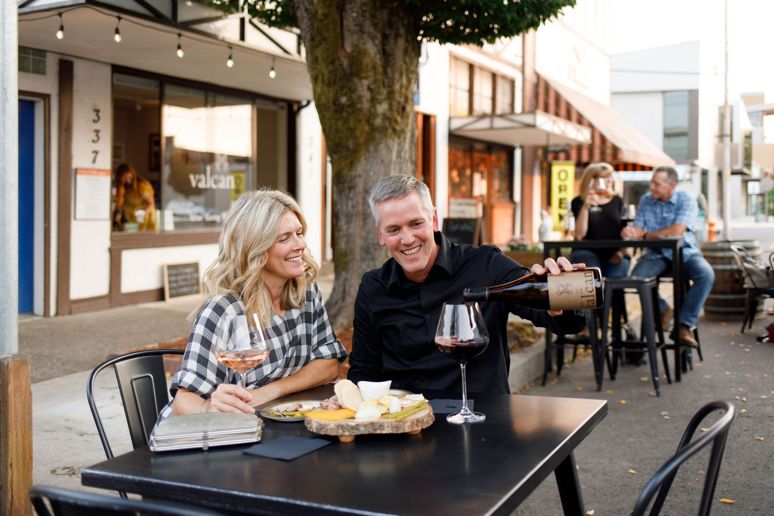 Older couple drinking wine outdoors at Valcan Cellars in Corvallis, Oregon