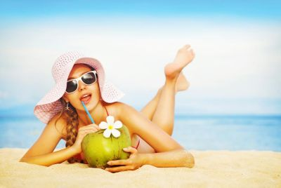 girl on beach drinking coconut water