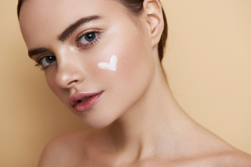 Close up of girl with white cream heart on the cheek