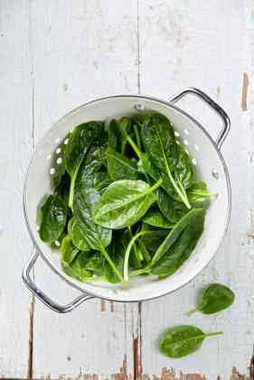 spinach in colander on table