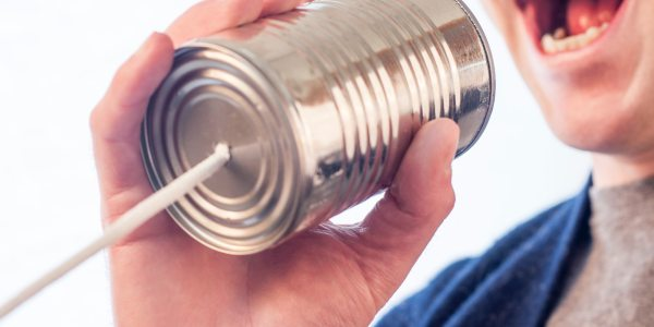 Image shows a woman talking into a metal can with a string attached and is representative of communication, or in this specific instance, communicating your Unique Selling Proposition to the market.