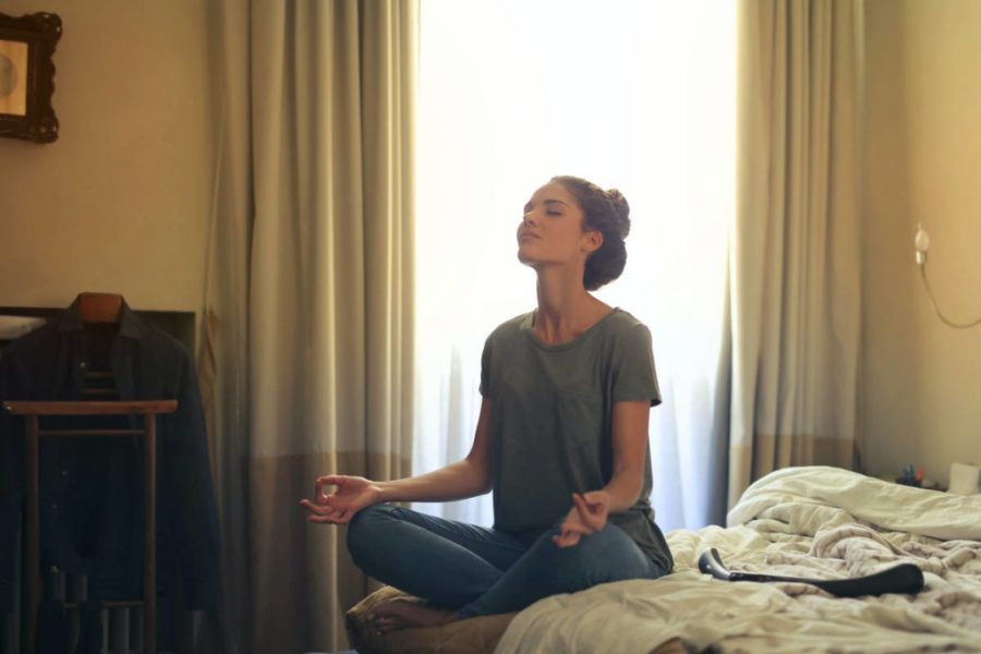 Women practicing pranayama meditation in bed with light coming through the window.