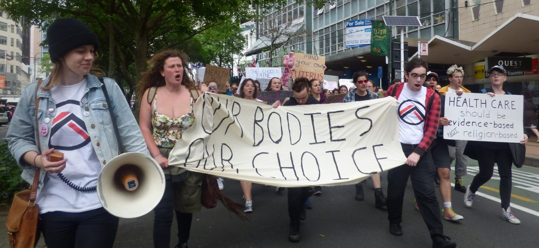"A march heading down Lambton Quay, on the road. The marchers - at least two wearing t-shirts with the Outer Alliance logo - are carrying a megaphone and banners/placards reading ""Our bodies, our choice"" and ""Healthcare should be evidence based nor religion based"""